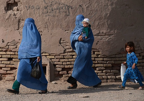 Afghan women walk with their children / Getty Images